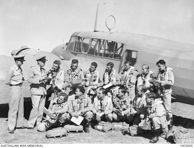 RAAF Trainees being briefed for an airborne signals training exercise in front of an Avro Anson aircraft at RAAF Ballarat circa 1944